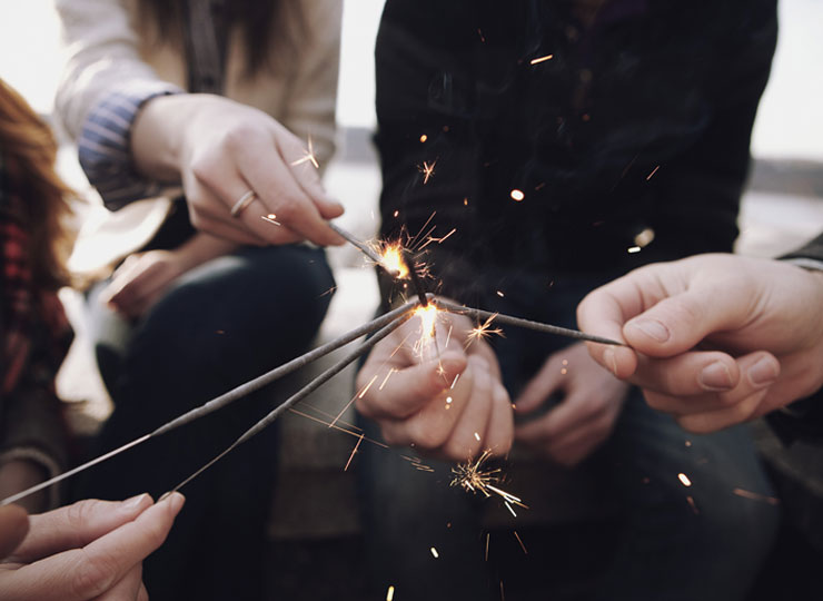 Multiple hands holding sparklers