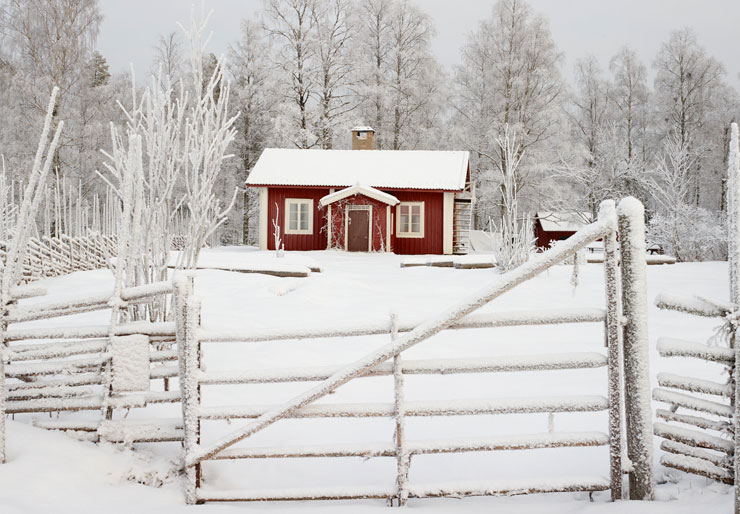 Small red wooden cabin in winter