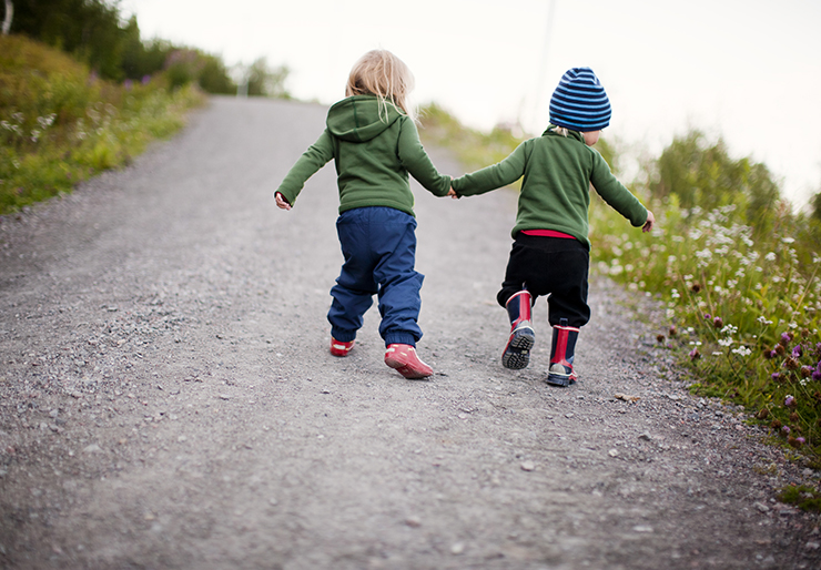 Two small kids holding hands while running outdoor.