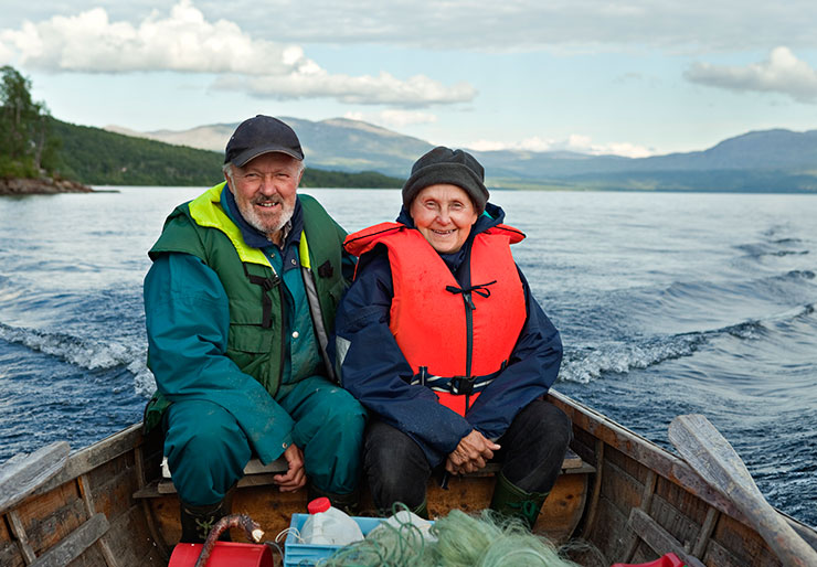 Smiling elderly couple in boat at sea